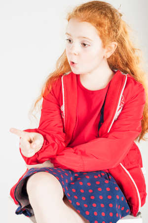 Pointing Little Red-haired Caucasain Girl with Surprised Expression. Vertical Image. photo