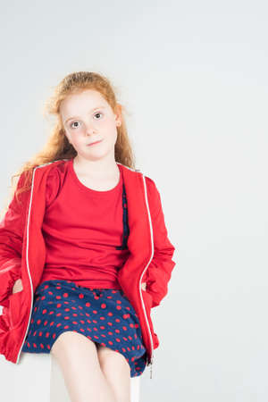 Fashionable Little Red-Haired Caucasian Girl In Studio. Against White Background. Vertical Image photo