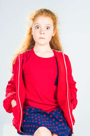 Portrait of Surprised Redhaired Caucasian Little Girl In Red Jacket and Polka dotted Skirt. Against White Background. Vertical Image photo