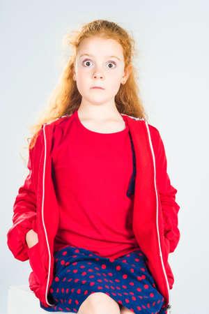 polka dotted: Retrato de raza cauc�sica pelirroja sorprendida Ni�a En Chaqueta Roja y punteada polca de la falda. Contra el fondo blanco. Vertical de la imagen