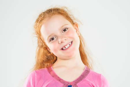 Portrait of Smiling Caucasian Redhaired Little Girl.Standing Against White.  Horizontal Image Composition photo