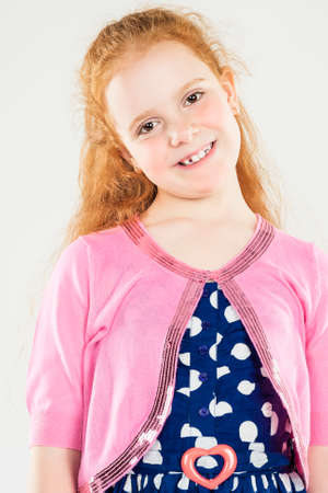 Smiling Caucasian Redhaired Little Girl.Standing Against White. Vertical Image Composition photo
