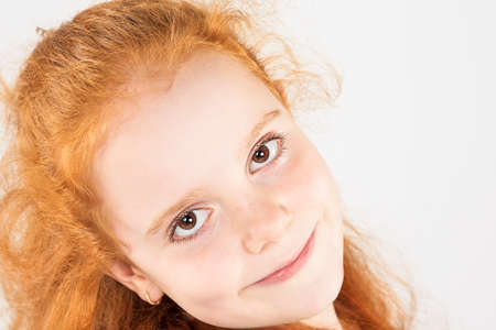 Closeup Natural Portrait of Little Red-haired Girl Looking Straight to the Camera. Against White Background. Horizontal Shot photo