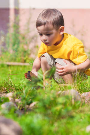 making a fire: Thoughtful Caucasian Little Boy Making Fire on the Firepace Outdoors. Horizontal Image Stock Photo