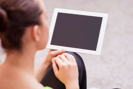 Back View Portrait of Woman Holding Tablet Computer. Focus on Tablet Computer. Horizontal Image Stock Photo