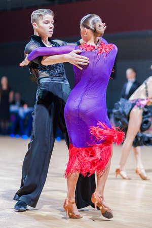 gold facial: Minsk-Belarus, December 20, 2014: Professional belarussian dance couple of Shmidt Danila and Gumenyuk Alina performs Youth-2 Latin-American program on Gold of The Capital International IDSA Tournament on December 20, 2014, in Minsk, Republic of Belarus