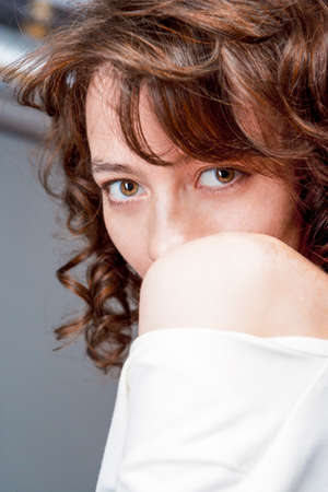 vertical image: Thoughtful Charming Cute Caucasian Female with Beautiful Dark Curly Hair. Vertical Image Stock Photo