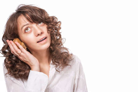 mistery: Positive Caucasian Female with Long Curly Hair Listening to Sea Shell. Surprised Facial Expression. Isolated Over Pure White Background.Horizonal Image Composition