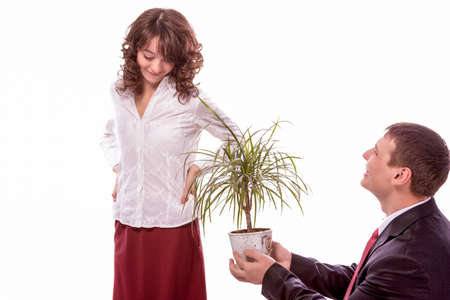 allegoric: Portrait of Caucasian Couple Together Having Fun. Allegoric Flower Gift Presentation to Female. Isolated Over White. Horizontal Image Composition