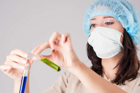 h1n1 vaccines: Closeup of Focused Caucasian Female Scientist Making Solution into the Glass Flask. Over Gray Background. Focus on Eyes. Horizontal Image Stock Photo