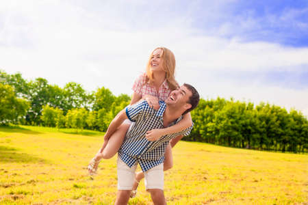Portrait of Happy Caucasian Couple Playing Outdoors in Summer. Having Fun While Piggybacking and Happiness Lifestyle Concept. Green Forest Environment. Horizontal Image Composition photo