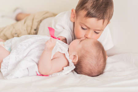 soft skin: Little Caucasian Boy Kissing His Newborn Sister. Indoors Shot. Horizontal Image