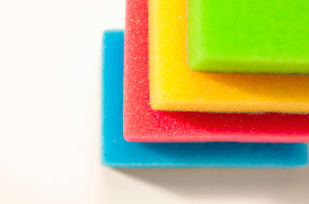 houseware: Kitchen Houseware and Utensils Concept: Colorful Sponges in One Stack Together. On a White Surface. Horizontal Image