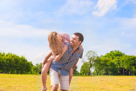 Youth Lifestyle, Summer Vacations, Dating, Love, Happiness Concepts. Happy caucasian Couple Piggybacking Outdoors. Against Nature Green Forest. Horizontal Image Composition photo