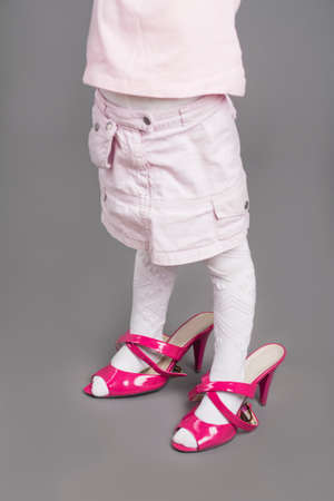 unsuitable: Closeup of Legs of Little Girl Trying On Mothers Unsuitable High Heel Shoes. Over Gray Background.Vertical Image
