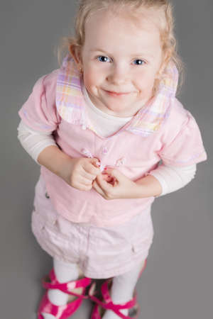 Portrait of Young Caucasian Little Girl Trying On Mothers Shoes and Smiling. Vertical Image Composition