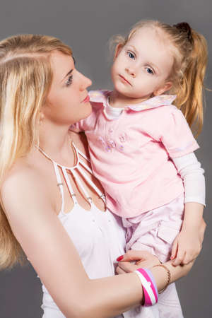 parental love: Closeup Portrait of Young Caucasian Female with Little Daughter Posing Together Embraced. Against Gray Background.Vertical Image Composition