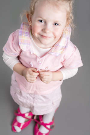 unsuitable: Portrait of Young Caucasian Little Girl Trying On Mothers Shoes and Smiling. Vertical Image Composition