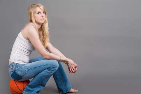 Sporty Caucasian Blond Female Sitting on Basketball Ball in Studio Environment. Horizontal Image Orientation photo
