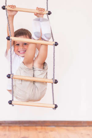 vertical image: Youth Concept: Happy Laughing Caucasian Little Boy Usiing Sport Equpment Indoors. Vertical Image