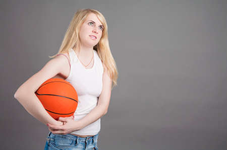 Portrait of Young Caucasian Blond Female  Posing in Studio with Basketball Ball. Horizontal Image Composition photo