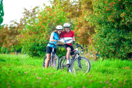 Sport and Fitness Concept. Happy caucasian Couple of Cyclists With Location Map Outdoors.Horizontal Image Composition