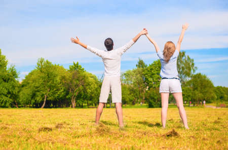 hand lifted: Young Caucasian Couple Standing Together on Grass Meadow with hands Lifted Up. Horizontal Image