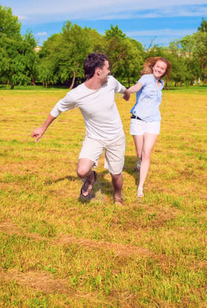 hands connected: Smiling Caucasian Couple Relaxing Outdoors and Having Fun Together. Running on Grass Meadow with Hands Connected. Vertical Image Orientation Stock Photo