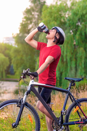 mountin: Sport and Cycling Concept: Young Caucasian Male Cyclist Having water Break Outdoors and Holding Mountin Bike. Vertical Image Composition