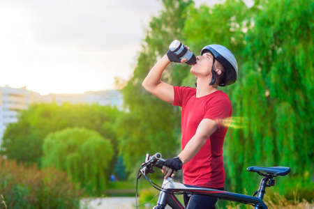 mountin: Cycling Concept: Young Caucasian Male Cyclist Having water Break Outdoors and Holding Mountin Bike.Horizontal Image Composition Stock Photo