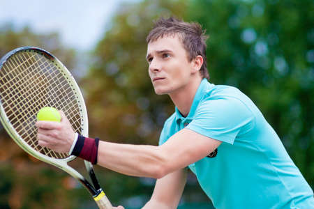 Raquet: Sport and Tennis Concept: Handsome Caucasian Man With Tennis Raquet Preparing to Serve Ball On Court. Horizontal image