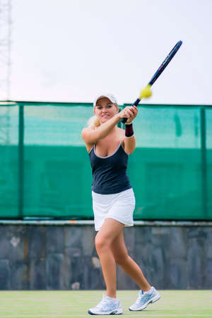 Professional Female Tennis Player in Action On Court. Vertical Image Orientation photo