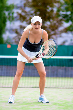 Sport and Fitness Concept: Professional Sexy Female Tennis Player With Raquet Standing On Courte Outdoors Prior to Serving Ball. Vertical Shot photo