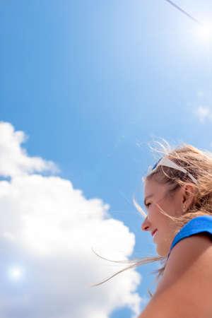 bluer: Closeup Portrait of Smiling Caucasian Blond Woman Against Summer Bluer Sky. Vertical Shot