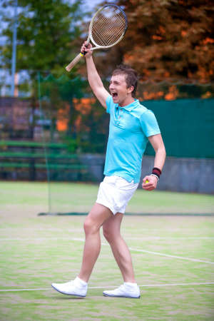 exclaiming: Tennis Sport Concept: Portrait of young Exclaiming Male Caucasian Tennis Player With Raquet Outdoors on Court.Vertical Image Composition Stock Photo