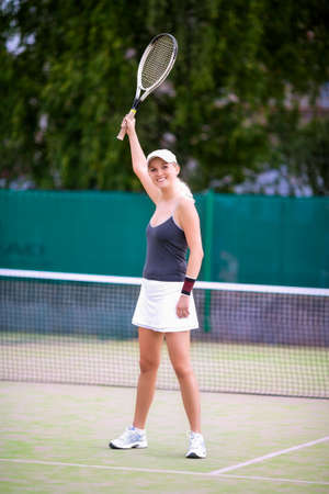 Portrait of Exclaiming Professional Tennis Player On Court Outdoors Holding Racquet Up. Positive Expression. Vertical image Composition photo
