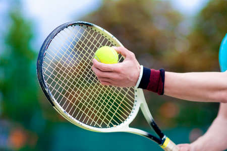 raquet: Closeup of Hands of Professional Male tennis Player Holding Raquet and Tennis Ball in Contact. Horizontal Image Composition