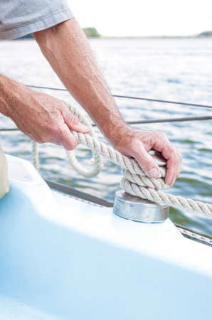 yachtsman: Closeup up of Yachtsman Hands Dealing with Yacht Ropes. Vertical Image Composition Stock Photo