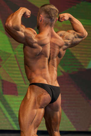 26: Minsk-Belarus, April, 26: Professional Male Caucasian Bodybuilder Performing on Stage during Bodybuilding and Fitness Championship of the Republic of Belarus on April, 26, 2015 in Minsk, Republic of Belarus