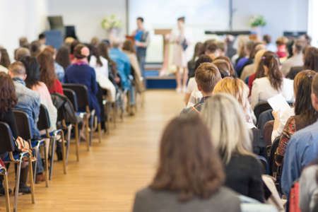 Two Hosts Speaking In front of the Large Group of People. Horizontal Image Composition