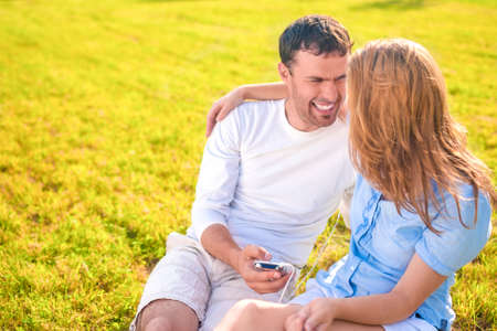 palmtop: Youth Lifestyle Concept: Laughing Caucasian Couple Sitting Together on the Grass Outdoors with palmtop Player. Listening to Music and Laughing. Horizontal Image Composition Stock Photo
