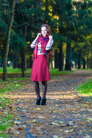 vertical orientation: Style and Fashion Concept and Ideas: Young Caucasian Female Brunette Woman in Made to Measure Clothing Standing in Autumn Forest Outdoors. Vertical Image Orientation Stock Photo