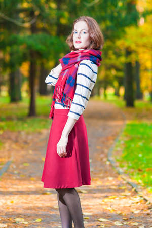 made to measure: Style and Fashion Concept and Ideas: Young Caucasian Female Brunette Woman in Made to Measure Clothing Standing in Autumn Forest Outdoors. Vertical Image Orientation Stock Photo