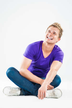 sexy image: Positive Smiling Handsome Guy. Sitting Against White. Vertical Image Composition