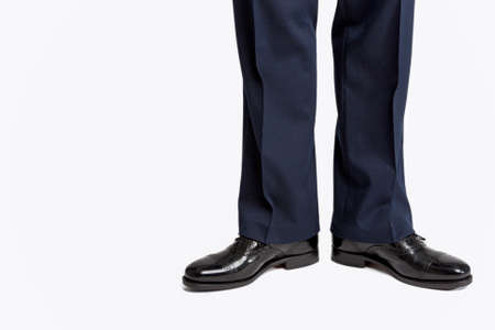 against white: Man in Stylish Black Shiny Male Semi-Brogue Posing in Direct Position Against White. Horizontal Image Orientation