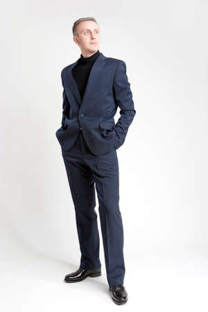 against white: Thinking Stylish Caucasian Man in Made to Order Suit. Posing Against White Background. Vertical Image Orientation