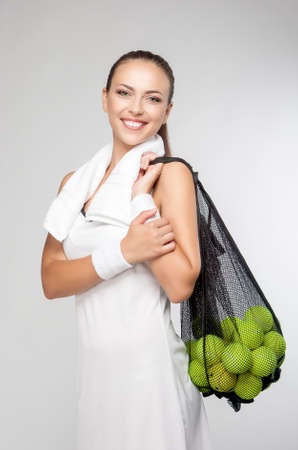 woman s bag: Healthy Lifestyle Concept: Closeup Portrait of Professional Female Tennis Player Holding Plenty of Balls in Mesh. Vertical Image Composition