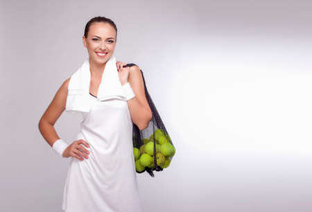 woman s bag: Sport Concept: Portrait of a Woman With Tennis Balls in Mesh Posing in Studio. Healthy Lifestyles. Horizontal Image Stock Photo