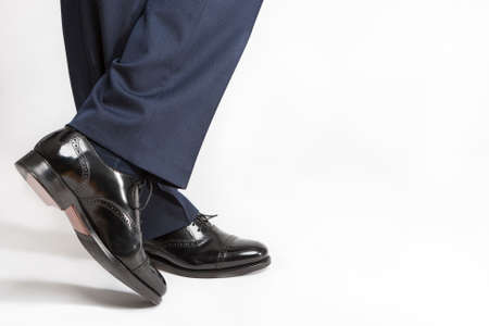 against white: Footwear Concept: Closeup of Stylish Black Shiny Male Semi-Brogue On Crossed Legs Against White. Horizontal Image Orientation