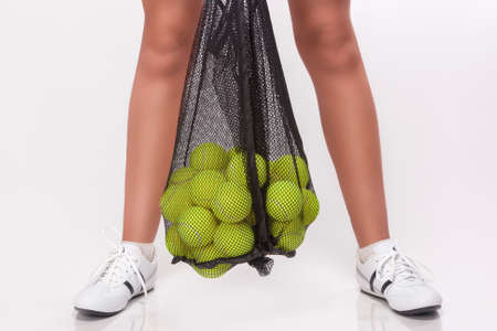 girl in sportswear: Closeup of Female Legs Holding Tennis Balls In Mesh in Studio Environment. Horizontal Image Composition